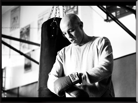 photo noir et blanc de Yann qui attache son gant de boxe
